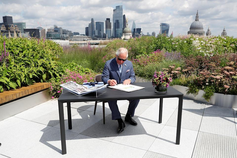 The Prince of Wales signs a document commemorating his visit to Goldman Sachs in central London (PA Wire)
