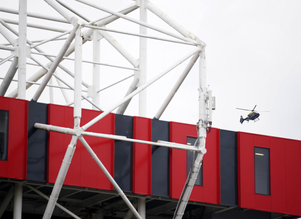 A police helicopter flies over the Old Trafford stadium before the English Premier League soccer match between Manchester United and Liverpool, in Manchester, England, Sunday, May 2, 2021. Manchester United supporters have stormed into the stadium and onto the pitch ahead of Sunday's game against Liverpool as fans gathered outside Old Trafford to protest against the ownership. (AP Photo/Dave Thompson, Pool)