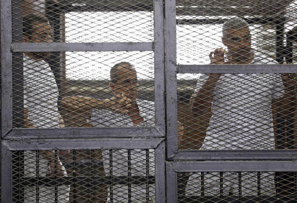 Al Jazeera journalists (L-R) Baher Mohamed, Peter Greste and Mohammed Fahmy stand behind bars in a court in Cairo in this June 1, 2014 file photo. Al Jazeera, the Qatari-funded television station whose reporting of the 2011 Arab Spring uprisings won it millions of viewers in the Middle East, is defiant following a backlash by Arab governments that accuse it of supporting Islamists. REUTERS/Asmaa Waguih/Files (EGYPT - Tags: POLITICS MEDIA CRIME LAW)