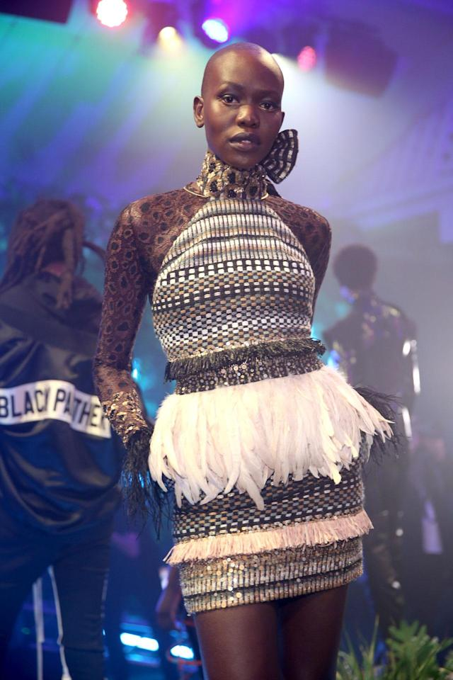 <p>Model wears a woven embroidered dress with feather waist band by Sophie Theallet at the Black Panther Welcome to Wakanda NYFW fashion presentation. (Photo: Courtesy of Marvel Studios Black Panther/Getty) </p>