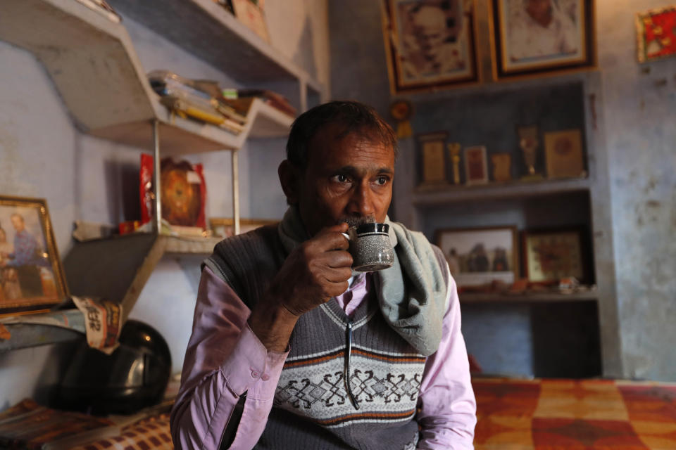 Indian farmer Ram Singh Patel drinks morning tea before leaving his village house to work in the field in Fatehpur district, 180 kilometers (112 miles) south of Lucknow, India, Saturday, Dec. 19, 2020. Patel's day starts at 6 in the morning, when he walks into his farmland tucked next to a railway line. For hours he toils on the farm, where he grows chili peppers, onions, garlic, tomatoes and papayas. Sometimes his wife, two sons and two daughters join him to lend a helping hand or have lunch with him. (AP Photo/Rajesh Kumar Singh)