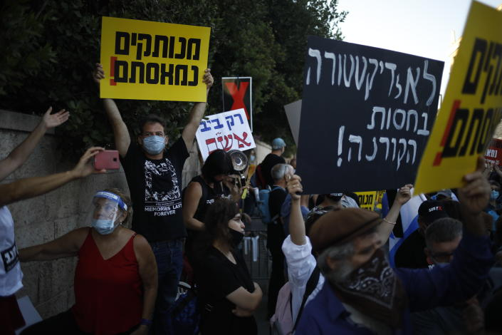 """Protesters, defying orders to maintain social distancing requirements, chant slogans outside of the Prime Minister's residence in Jerusalem, Tuesday, July 14, 2020. Thousands of Israelis demonstrated outside the official residence of Prime Minister Benjamin Netanyahu, calling on the embattled Israeli leader to resign as he faces a trial on corruption charges and grapples with a deepening coronavirus crisis. The signs read: """"No to dictatorship under the shelter of the Coronavirus,"""" and """"you are detached. We are fed up."""" (AP Photo/Ariel Schalit)"""