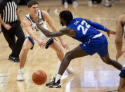 Villanova guard Collin Gillespie (2) passes the ball past Seton Hall guard Myles Cale (22) during the first half of an NCAA college basketball game, Tuesday, Jan. 19, 2021, in Villanova, Pa. (AP Photo/Laurence Kesterson)