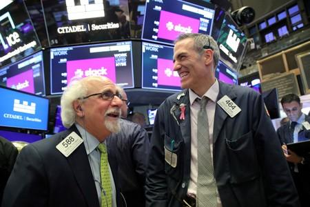 FILE PHOTO: Traders work on the floor during The Slack Technologies Inc. direct listing at the New York Stock Exchange (NYSE) in New York
