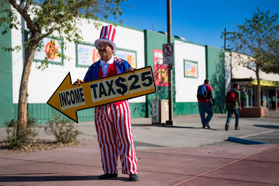 Jose (only first name given) advertises for a income tax shop dress as Uncle Sam on a corner in San Luis, Arizona, on February 15, 2017 near the US/Mexico border. Attention Editors, this image is part of an ongoing AFP photo project documenting the life on the two sides of the US/Mexico border simultaneously by two photographers traveling for ten days from California to Texas on the US side and from Baja California to Tamaulipas on the Mexican side between February 13 and 22, 2017. You can find all the images with the keyword : BORDERPROJECT2017 on our wire and on www.afpforum.com / AFP / JIM WATSON        (Photo credit should read JIM WATSON/AFP via Getty Images)