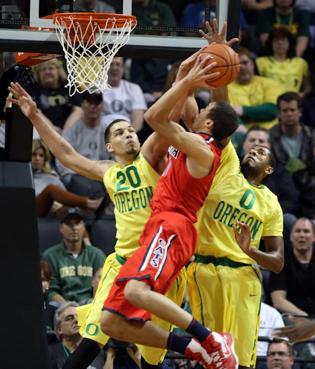 Oregon's Waverly Austin, left, fouls Arizona's Aaron Gardon as he defends the basket with teammate Oregon's Mike Moser, right, during the first half of an NCAA college basketball game in Eugene, Ore. on Saturday, March 8, 2014. (AP Photo/Chris Pietsch)