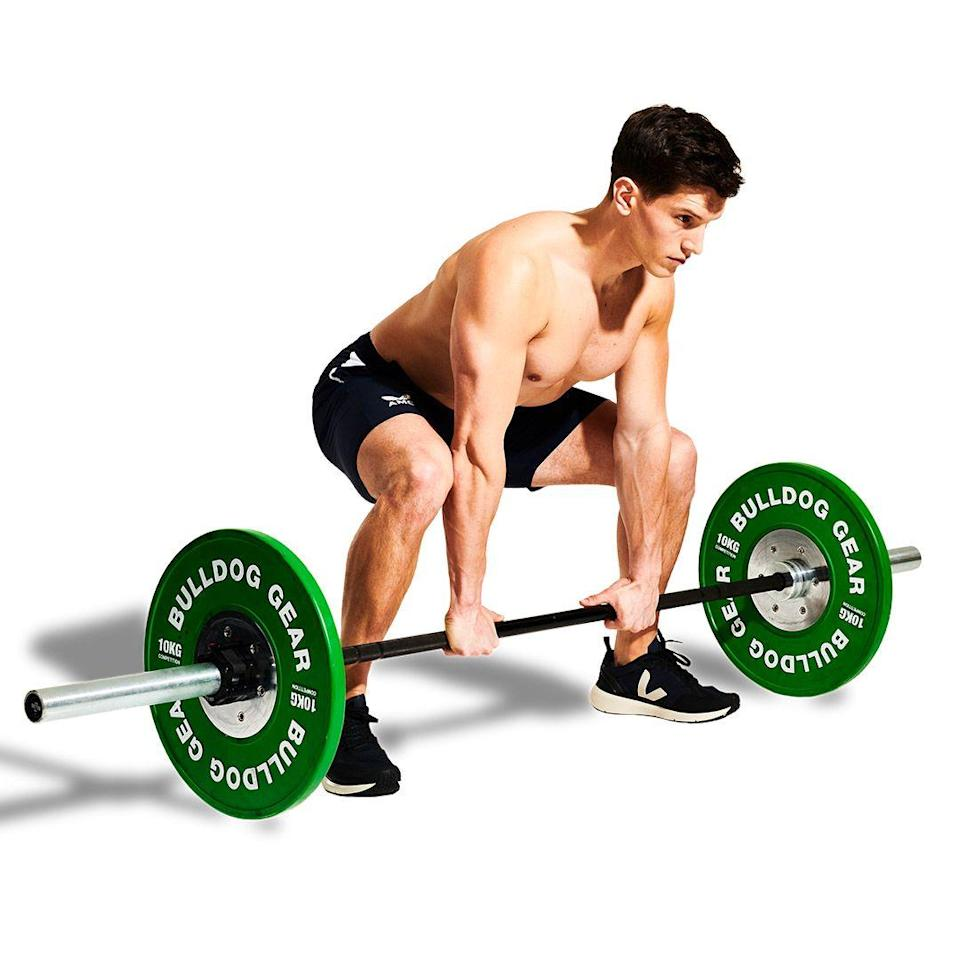 """<p>Stand with your feet just wider than your shoulders. Hinge at your hips and bend your knees to grasp the <a href=""""https://www.menshealth.com/uk/gym-wear/g33819895/best-home-barbells/"""" rel=""""nofollow noopener"""" target=""""_blank"""" data-ylk=""""slk:barbell"""" class=""""link rapid-noclick-resp"""">barbell</a>. Your grip should be narrow, with your arms between your legs.</p>"""