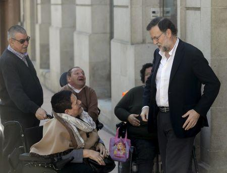 Spain's acting Prime Minister Mariano Rajoy talks to some people in wheelchairs on arrival at the Popular Party's provincial congress in Pontevedra in northwest Spain March 13, 2016. REUTERS/Miguel Vidal
