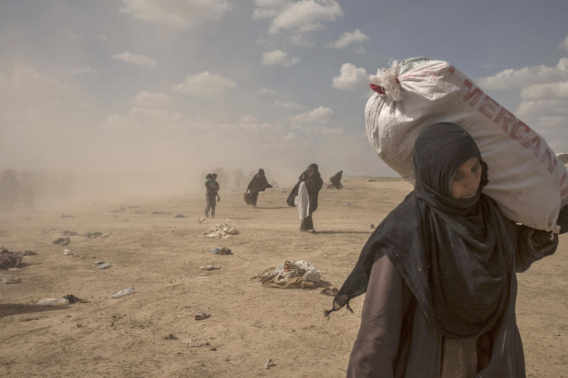 In this Wednesday, March 6, 2019, photo, a woman carries supplies from a reception area for people evacuated from the last shred of territory held by Islamic State militants, outside Baghouz, Syria. (AP Photo/Gabriel Chaim)