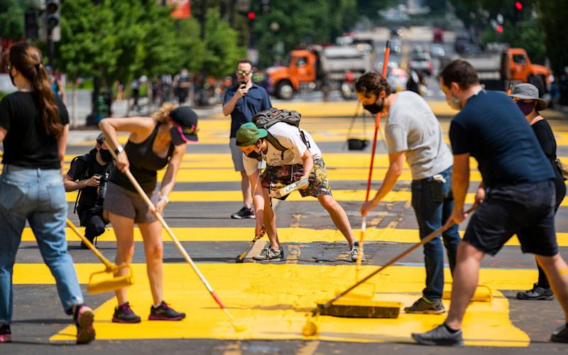 With permission from the city, volunteers paint 'Black Lives Matter' on 16th St. across from the White House - Shutterstock