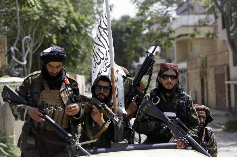 Taliban fighters display their flag while holding weapons in Kabul. Source: AP Photo/Rahmat Gul