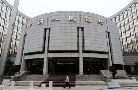 FILE PHOTO: A staff member walks in front of the headquarters of the People's Bank of China, the central bank, in Beijing