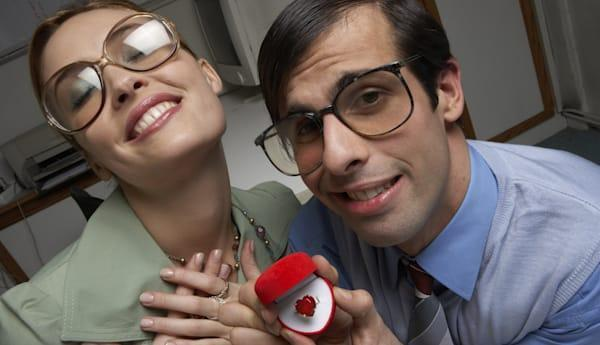 Male office worker presenting heart ring to female colleague, portrait