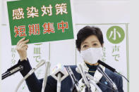 "Tokyo Gov. Yuriko Koike speaks during a news conference Wednesday, Nov. 25, 2020, in Tokyo. The board reads ""infection control measures, Short and intensive."" (Kyodo News via AP)"