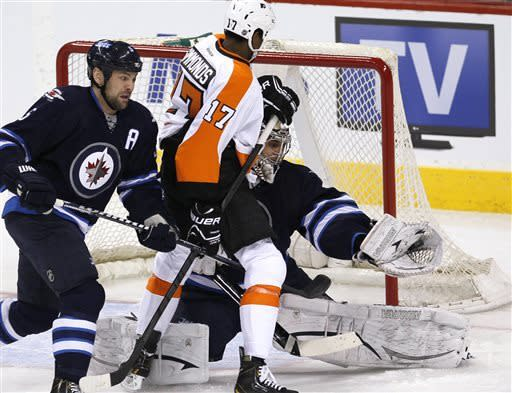 Winnipeg Jets goaltender Ondrej Pavelec makes a save as Philadelphia Flyers forward Wayne Simmonds and Jets defenseman Mark Stuart fight for position during the first period of an NHL hockey game action in Winnipeg on Saturday, April 6, 2013. (AP Photo/The Canadian Press, John Woods)