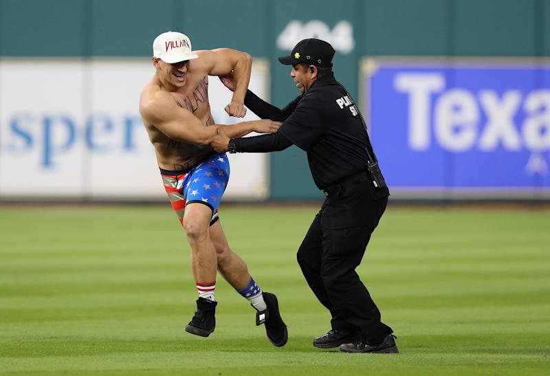Security apprehends a man during Game 5 of the 2017 World Series between the Houston Astros and the Los Angeles Dodgers on Oct. 29, 2017, in Houston, Texas.