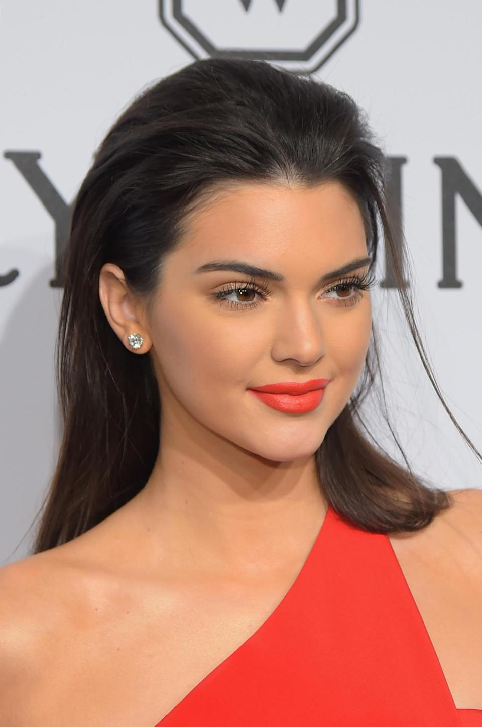 <p>At the amfAR New York Gala, Jenner was a classic bombshell in red lipstick that matched her gown, diamond studs, spider lashes, and hair brushed back. <i>(Photo: Getty Images)</i></p>