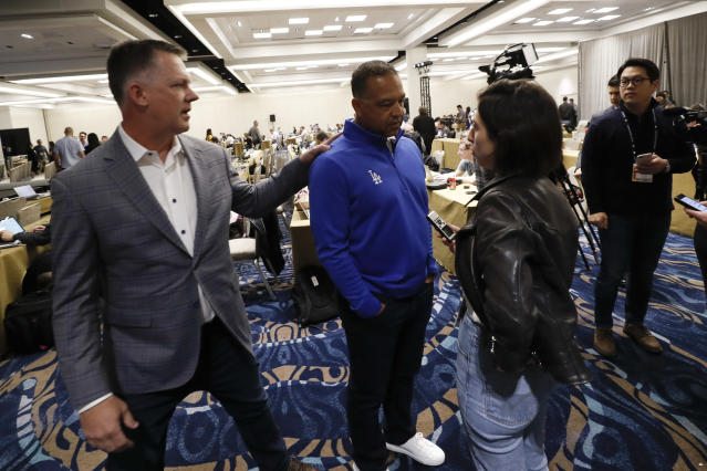Houston Astros manager A.J. Hinch, left, greets Los Angeles Dodgers manager Dave Roberts, center, during the Major League Baseball winter meetings, Tuesday, Dec. 10, 2019, in San Diego. (AP Photo/Gregory Bull)