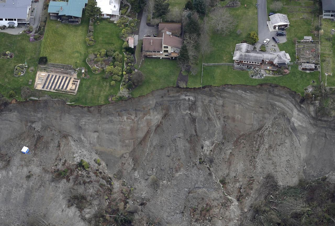 In this aerial photo, houses sit near the edge of a landslide, near Coupeville, Wash. on Whidbey Island, Wednesday, March 27, 2013. The slide severely damaged one home and isolated or threatened more than 30 on the island, about 50 miles north of Seattle in Puget Sound. No one was reported injured in the slide, which happened at about 4 a.m. Wednesday. (AP Photo/Ted S. Warren)