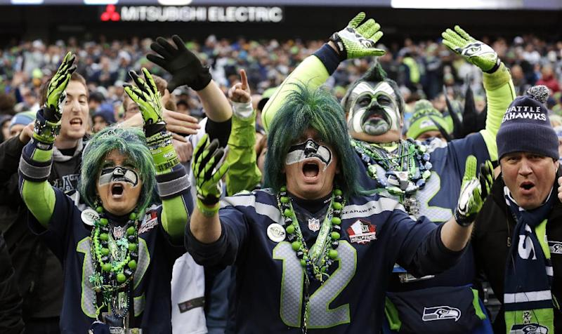 Seattle Seahawks fans cheer late in the second half of an NFL football game against the St. Louis Rams, Sunday, Dec. 29, 2013, in Seattle. The Seahawks won 27-9. (AP Photo/Elaine Thompson)