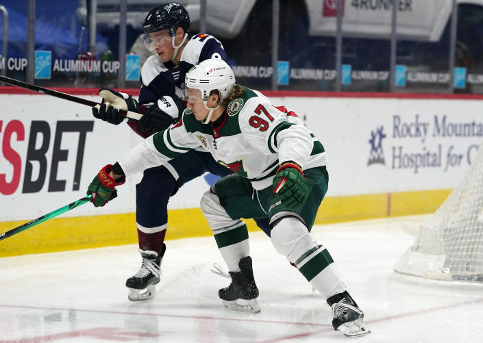 Minnesota Wild left wing Kirill Kaprizov, front, fights for control of the puck with Colorado Avalanche defenseman Cale Makar in the second period of an NHL hockey game Saturday, March 20, 2021, in Denver. (AP Photo/David Zalubowski)