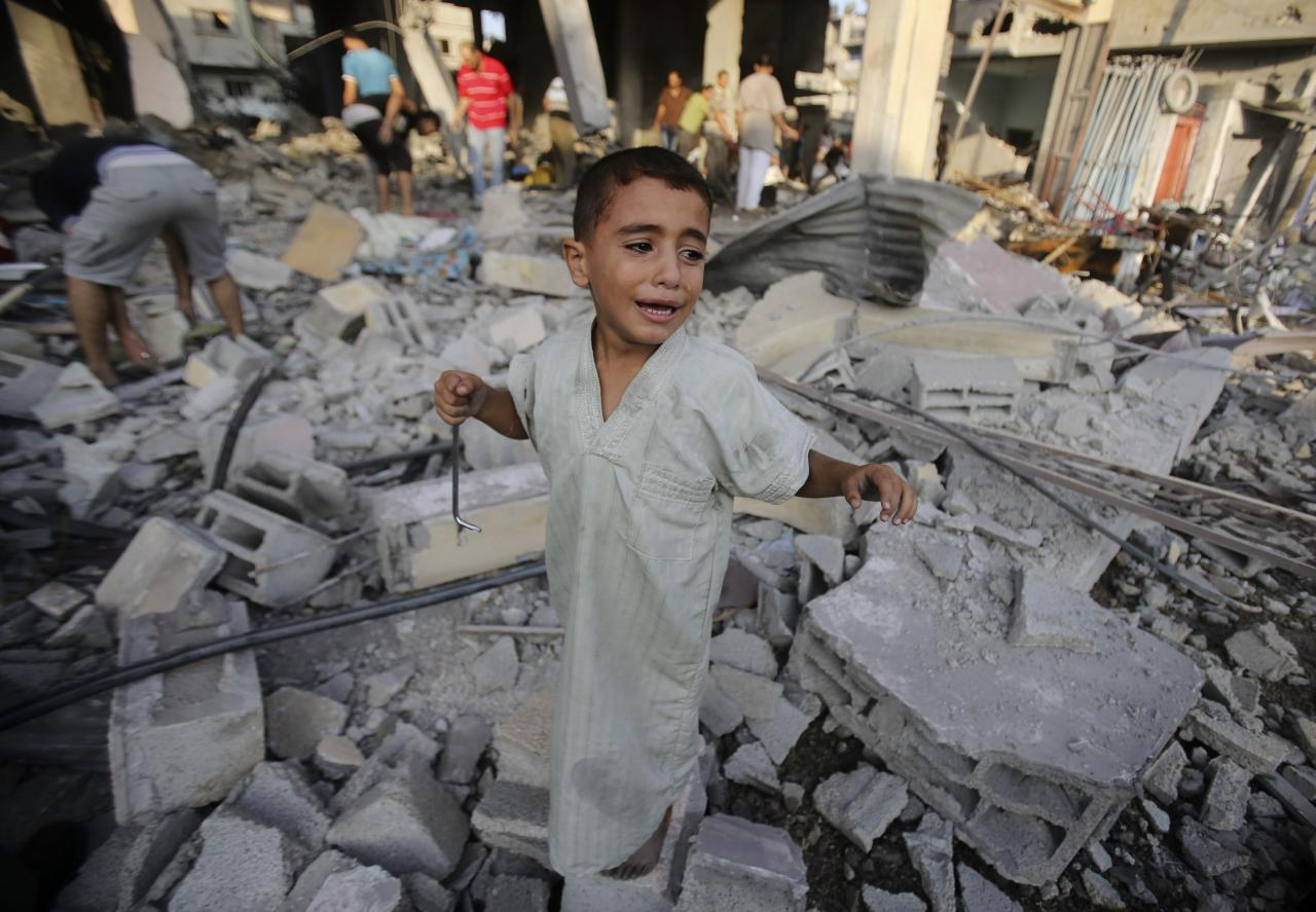A Palestinian boy cries as he stands in a debris-strewn street near his family's house, which witnesses said was damaged by an Israeli air strike in Rafah in the southern Gaza Strip August 26, 2014. Israeli air strikes launched before dawn on Tuesday killed two Palestinians and destroyed much of one of Gaza's tallest apartment and office buildings, setting off huge explosions and wounding 20 people, Palestinian health officials said. Israel had no immediate comment on the attacks that took place as Egyptian mediators stepped up efforts to achieve an elusive ceasefire to end seven weeks of fighting. Israel launched an offensive on July 8, with the declared aim of ending rocket fire into its territory. REUTERS/Ibraheem Abu Mustafa (GAZA - Tags: POLITICS CIVIL UNREST TPX IMAGES OF THE DAY)