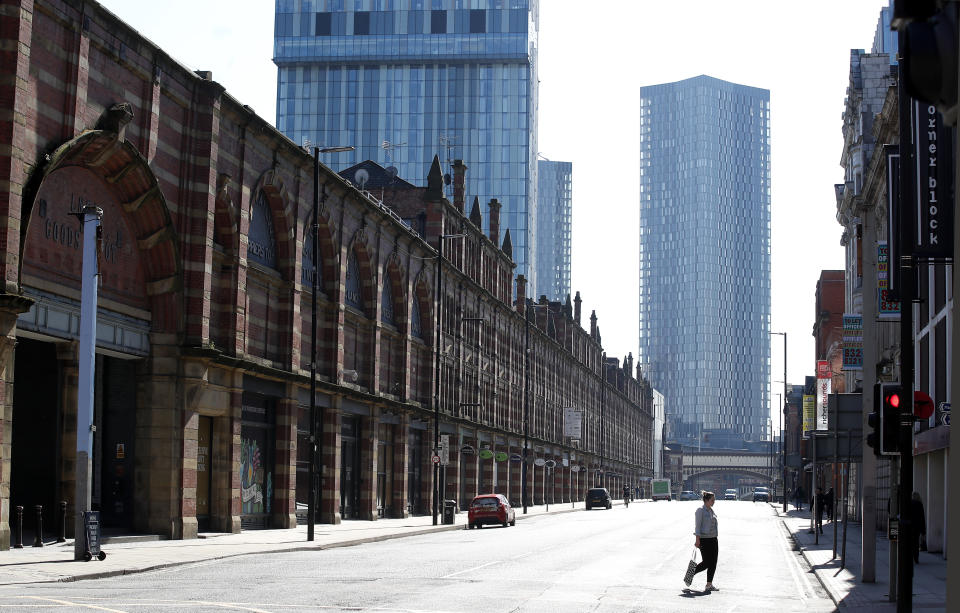A woman walks down a deserted Deansgate in Manchester after Prime Minister Boris Johnson has put the UK in lockdown to help curb the spread of the coronavirus.