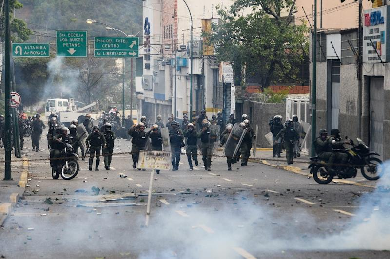 Riot police and opposition activists clash in Caracas on April 10, 2017 after Venezuela's political crisis intensified following the Supreme Court's ruling that curbed the powers of the opposition-controlled legislature