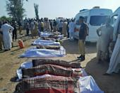 The bodies of victims from Monday's train accident are laid out next to the road in Daharki in Sindh province