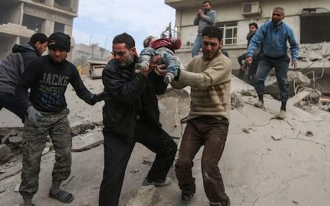 A man hands over a child to his father after being rescued from beneath the ruins of a building that collapsed following air strikes in besieged Eastern Ghouta - Credit: AFP