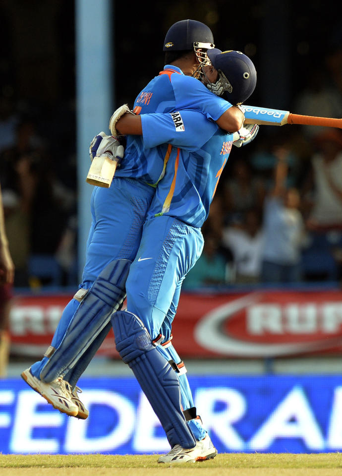 Indian cricket team captain Mahendra Sing Dhoni (L) is lifted off the ground by his teammate Ishant Sharma after hitting a boundary for six runs to seal their victory during the final match of the Tri-Nation series between India and Sri Lanka at the Queen's Park Oval stadium in Port of Spain on July 11, 2013. India defeated Sri Lanka by 1 wicket to win the series. AFP PHOTO/Jewel Samad