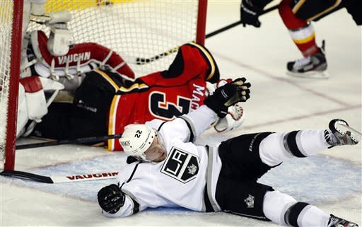 Los Angeles Kings' Trevor Lewis, right, crashes to the ice after colliding with Calgary Flames goalie Joey MacDonald during the second period of their NHL hockey game, Wednesday, Feb. 20, 2013, in Calgary, Alberta. (AP Photo/The Canadian Press, Jeff McIntosh)