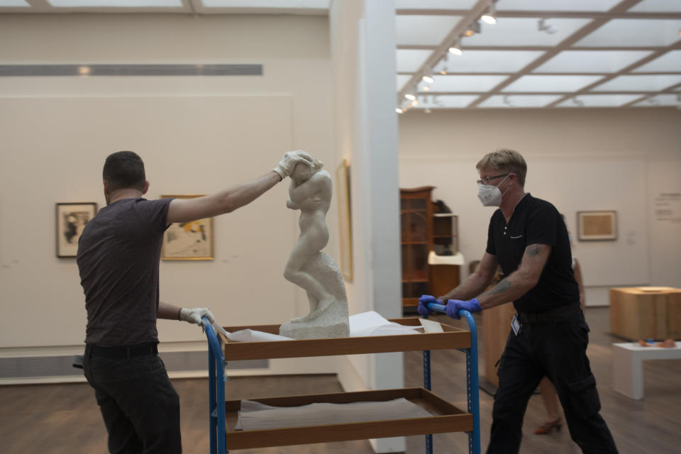 """Israel Museum staff move Auguste Rodin's """"Eve,"""" back into a gallery during final preparations to reopen following five months of closure due to the coronavirus pandemic, in Jerusalem, Tuesday, Aug. 11, 2020. The Israel Museum, the country's largest cultural institution, is returning the priceless Dead Sea scrolls and other treasured artworks to its galleries ahead of this week's reopening to the public. (AP Photo/Maya Alleruzzo)"""