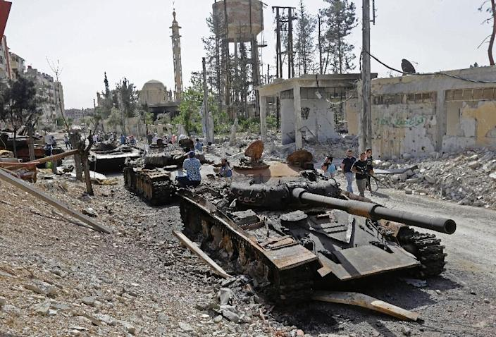 Destroyed tanks and armoured personnel carriers are pictured on a road in the Eastern Ghouta town of Douma on the outskirts of Damascus on April 20, 2018 (AFP Photo/LOUAI BESHARA)