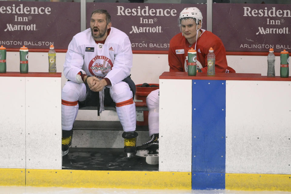 Washington Capitals left wing Alex Ovechkin, left, and defenseman Dmitry Orlov (9) watch during a drill at practice at the team's NHL hockey training camp, Thursday, Sept. 23, 2021, in Arlington, Va. (AP Photo/Nick Wass)