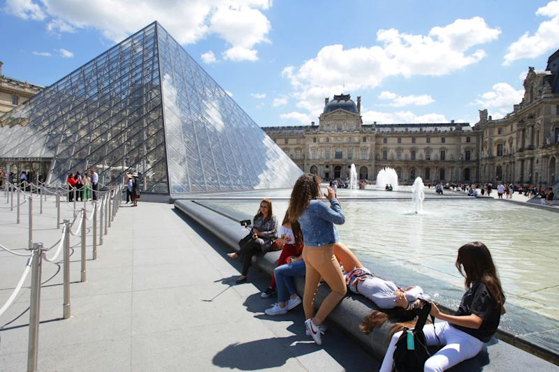Tourists enjoying the heat at the Louvre Museum in Paris (Picture: Getty)