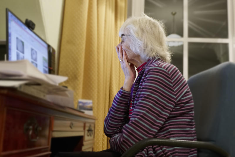 Old elderly senior person learning computer and online internet skills protect money scam and fraud uk