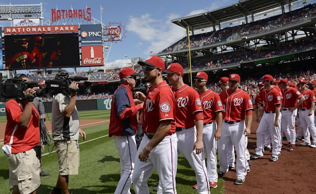 Washington National manager Davey Johnson, third from left, greets him team during a ceremony honoring himself before a baseball game against the Miami Marlins at Nationals Park in Washington, Sunday, Sept. 22, 2013. Johnson announced earlier in the season that this would be his last year managing the team. The Nationals organization paid tribute to him before the game, presenting him with a video tribute and a crystal award. (AP Photo/Susan Walsh)