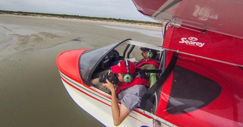 Photographer taking photos with camera out of seaplane window while flying in Southeastern U.S.