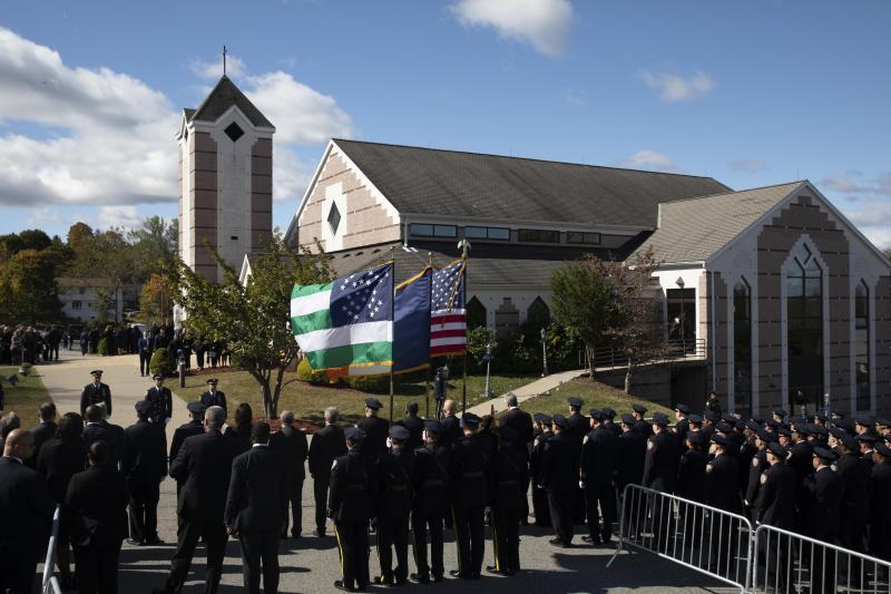 Police officers line the street in front of Church of the Sacred Heart, Friday, Oct. 4, 2019 in Monroe, N.Y., for the funeral service for New York City Police Officer Brian Mulkeen. Authorities say Mulkeen was fatally hit Sunday by two police bullets while struggling with an armed man in the Bronx. He is the second New York City officer killed by friendly fire this year. (AP Photo/Mark Lennihan)