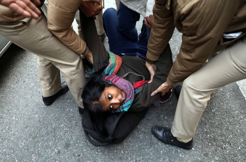 A demonstrator reacts as she is detained by police during a protest against a new citizenship law, in New Delhi