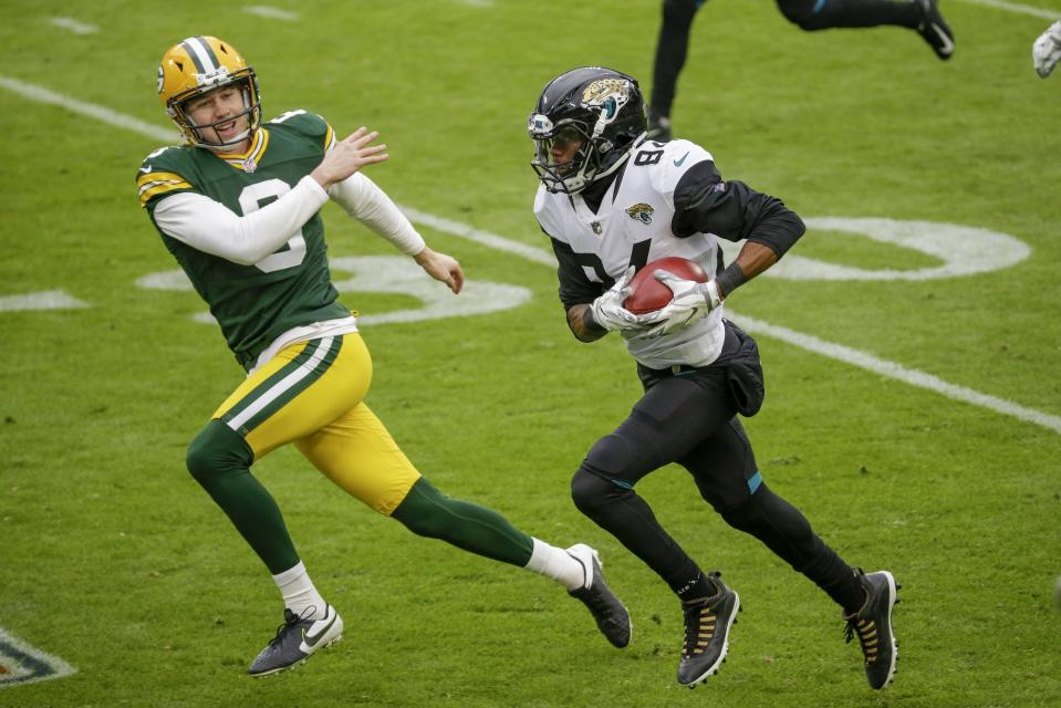 Green Bay Packers punter J.K. Scott can't stop Jacksonville Jaguars' Keelan Cole as he runs a punt back for a touchdown during the first half of an NFL football game Sunday, Nov. 15, 2020, in Green Bay, Wis. (AP Photo/Mike Roemer)