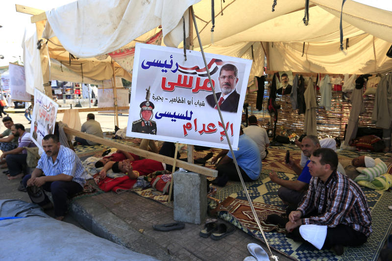 "Supporters of Egypt's ousted President Mohammed Morsi are seen under a tent as gathering for funeral of Omar Mohammad al-Sayyid, 19, who was killed on early July 24, 2013 during clashes between supporters and opponents of Egypt's Islamist President Mohammed Morsi, at Nasr City where protesters have installed their camp and hold their daily rally, in Cairo, Egypt, Thursday, July 25, 2013. Arabic on the banner at reads, ""Morsi my president,"" and ""the execution for el-Sissi."" The Muslim Brotherhood's leader on Thursday made an unusually harsh attack on Egypt's military chief, saying his ouster of President Mohammed Morsi was a worse crime than even destroying the Kaaba, Islam's holiest shrine.(AP Photo/Hassan Ammar)"