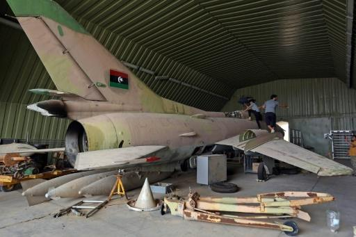 Fighters loyal to Libya's UN-recognised Government of National Accord (GNA) climb over a partially disassembled MiG 23 aircraft, after seizing Al-Watiya airbase  southwest of the capital Tripoli, on May 18, 2020