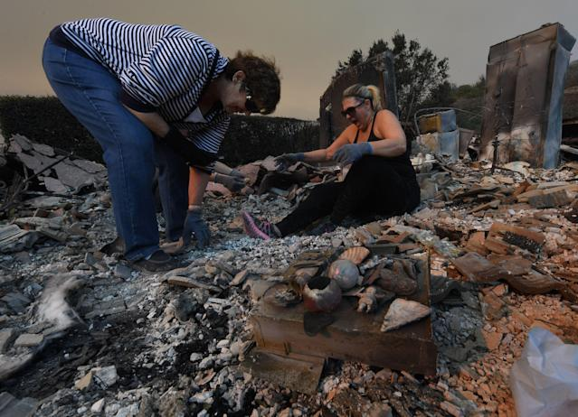 <p>Members of the Reinhardt family sort through the remains of their family home after the Thomas wildfire swept through Ventura, California on Dec. 6, 2017. (Photo: Mark Ralston/AFP/Getty Images) </p>