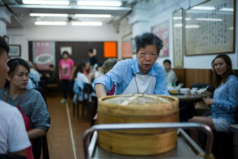 "Steamed dim sum dishes are distributed by fierce looking ""trolley aunties"""
