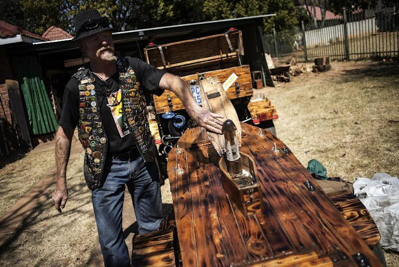 Biker and former prison warder, Rusty Poole, shows a gadget attached to his coffin-shaped trailer, near his home in Cullinan, South Africa, on August 27, 2014 (AFP Photo/Gianluigi Guercia)