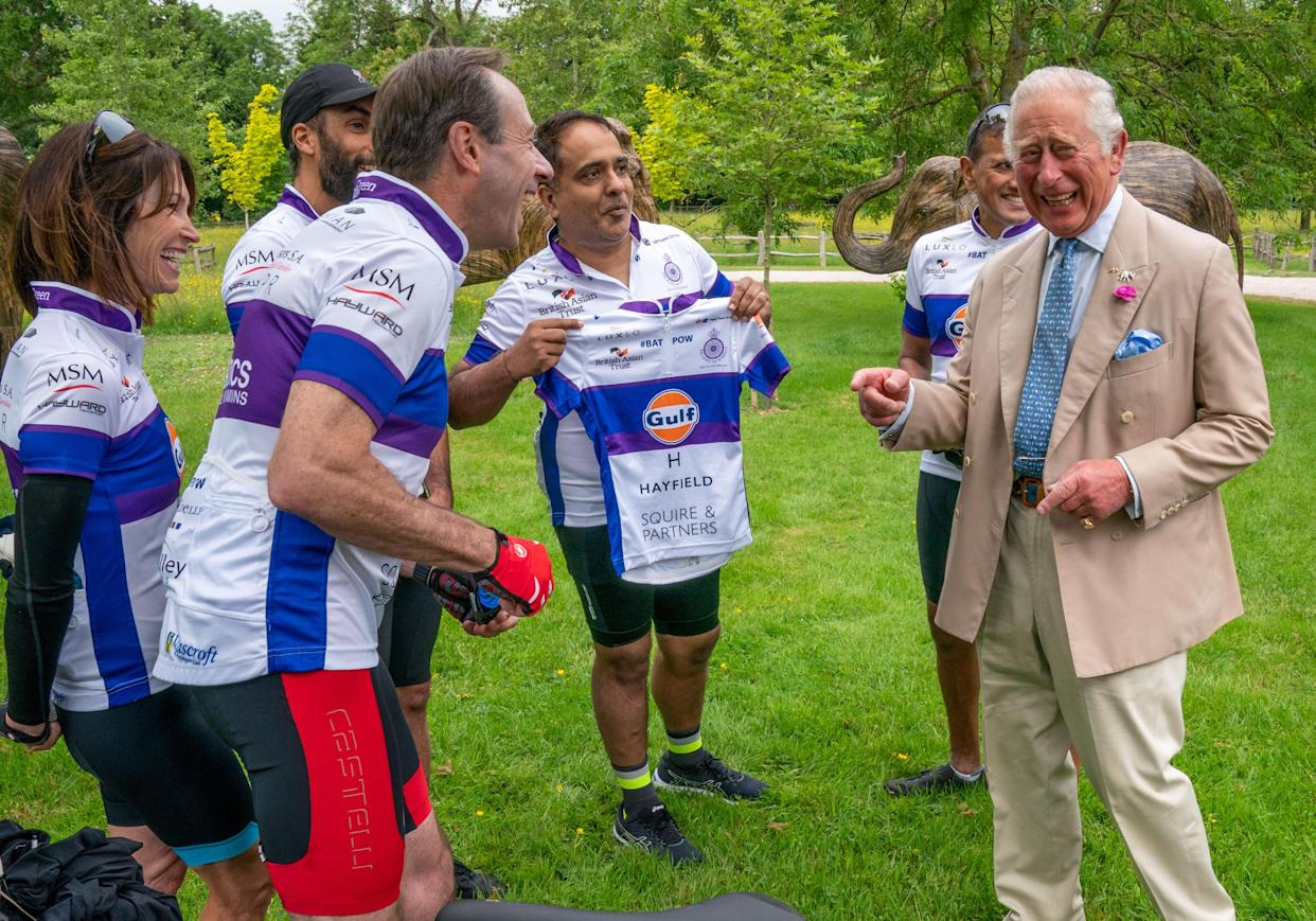 Rohit Chaddapresents the Prince of Wales with a cycling vest, which was two sizes too small, before he joined representatives of the British Asian Trust at Highgrove in Gloucestershire before they embark on the charity's 'Palaces on Wheels' cycling event. Picture date: Thursday June 10, 2021.