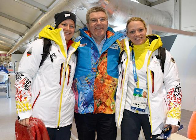 IOC President Thomas Bach poses with German Ice Hockey players Franziska Busch, left, and Susann Goetz as he visits the Athletes Olympic Village prior to the 2014 Winter Olympics on Saturday, Feb. 1, 2014 in Sochi, Russia. The games run from Feb. 7-23. (AP Photo/Pascal Le Segretain, Pool)