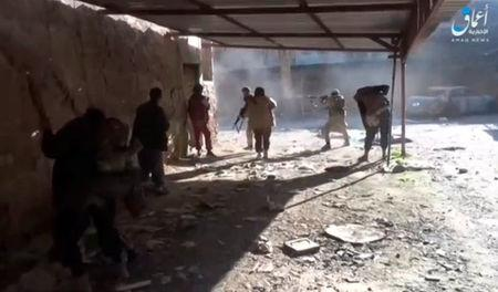 A still image taken from a video posted to a social media website by the Islamic State-affiliated Amaq News Agency on March 26, 2017, shows men, said to be Islamic State fighters, firing their weapons, said to be in Western Mosul